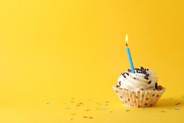 Cupcake mit kerze auf gelbem hintergrund, platz für text