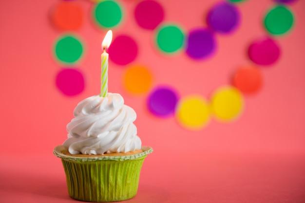 Cupcake mit kerze auf rosa feierpartyhintergrund