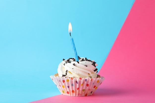 Cupcake mit kerze auf zweifarbigem hintergrund, platz für text