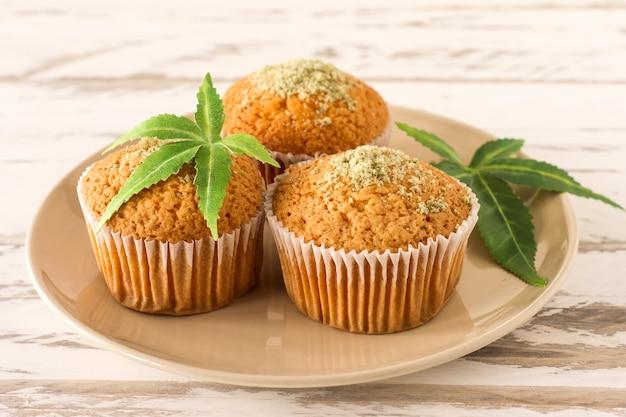 Cupcake mit marihuana. leckere cupcake-muffins mit cannabis-unkraut-cbd. medizinische marihuana-medikamente in lebensmitteldesserts, ganja-legalisierung.