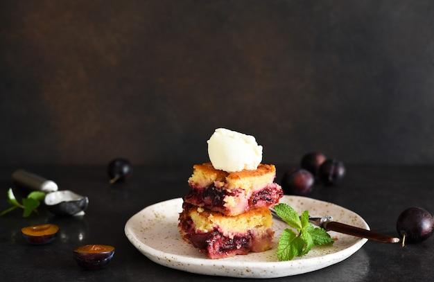 Cupcake mit pflaumen und vanilleeis auf dunklem hintergrund. obstkuchen mit minze.