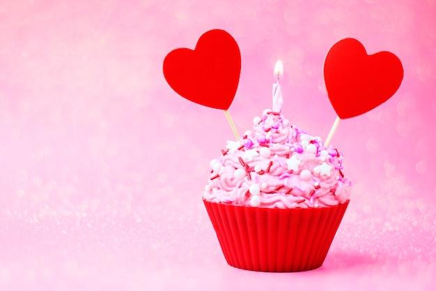Cupcake mit rosa creme, rotem herzen und wunderkerze auf einem rosa hintergrund. essen zum valentinstag.