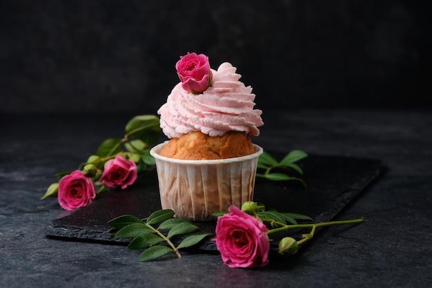 Cupcake mit rosen verziert. dessert auf einer schwarzen schieferplatte. kuchen auf dunklem hintergrund.
