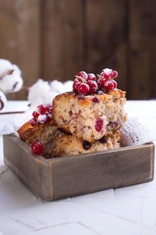 Cupcake mit roten johannisbeeren bestreut mit weißem zucker pulver, auf einem holzbrett und weißem hintergrund, baumwolle blumen