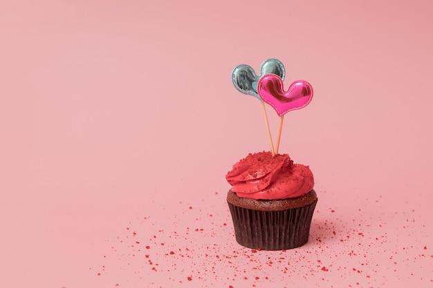 Cupcake mit roter creme und dekorieren zwei herzen für valentinstag-banner mit kopienraum