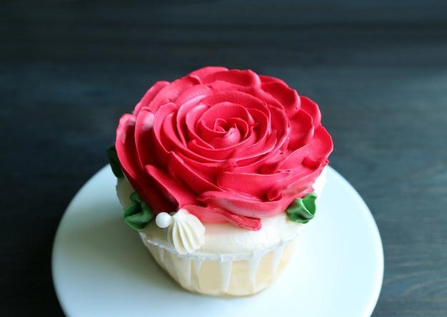 Cupcake mit roter rosafarbener schlagsahne verziert