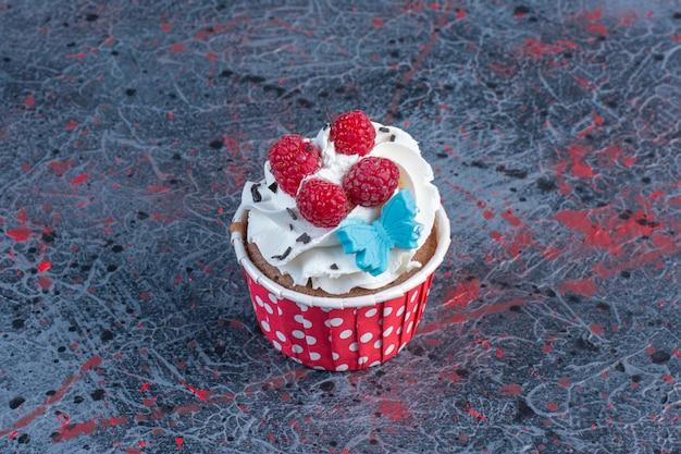 Cupcake mit sahne in einem pastetchenet auf abstraktem tisch.
