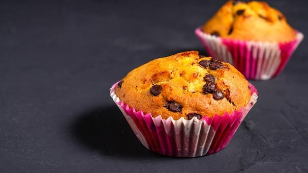 Cupcake mit schokoladenstücken auf einer dunklen oberfläche