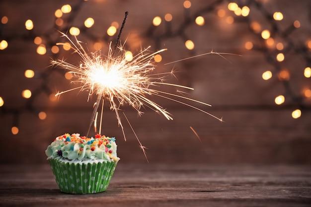 Cupcake mit wunderkerze auf altem hölzernen hintergrund
