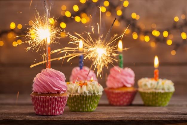 Cupcake mit wunderkerze auf altem holztisch