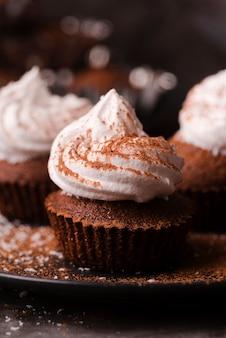 Cupcake mit zuckerguss und kakaopulver