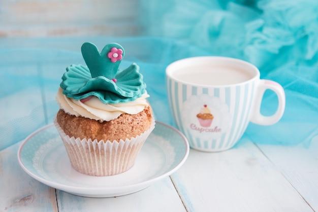 Cupcake und eine tasse auf türkisfarbenem hintergrund. hellblauer holztisch