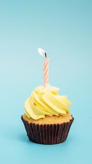 Cupcake und kerze auf blauem grund.