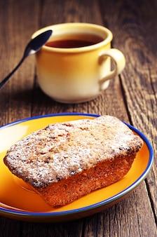 Cupcake und tasse tee auf dem tisch