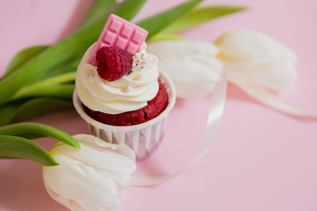 Cupcake und tulpen auf rosa. leckere kuchen