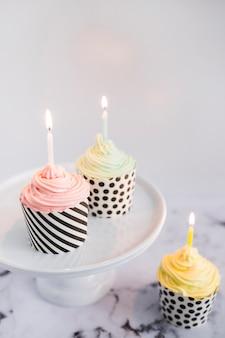 Cupcakes auf dem display mit hellen kerzen