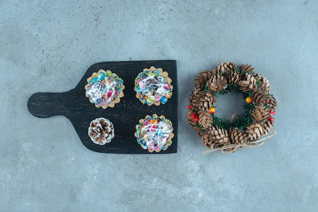 Cupcakes auf einem brett neben einem kranz auf marmoroberfläche
