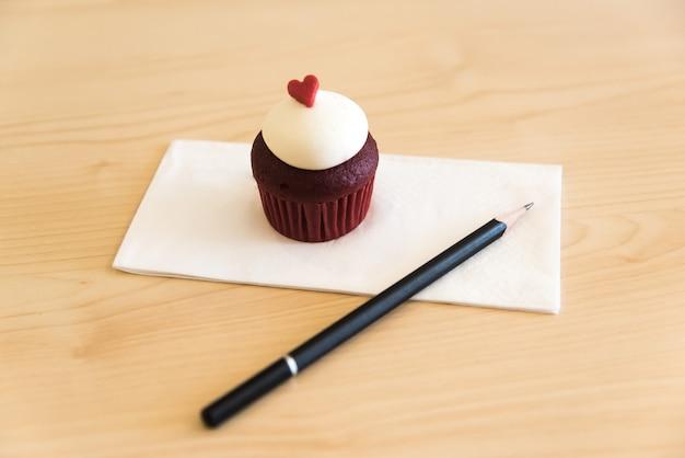 Cupcakes aus rotem samt mit frischkäse-zuckerguss, verziert mit schokoladenherz