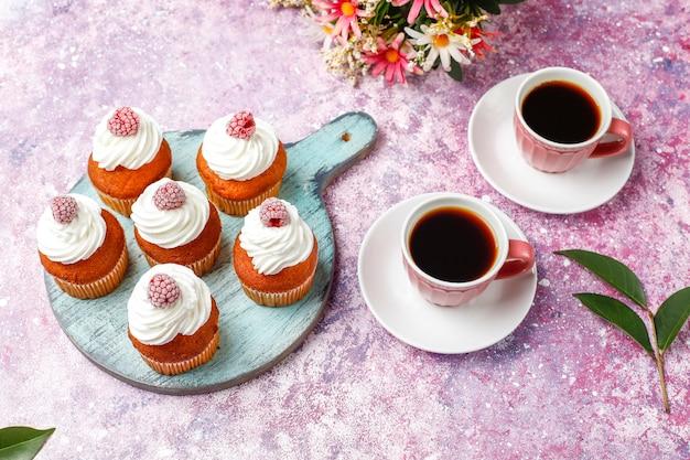 Cupcakes dekorierten schlagsahne und gefrorene himbeeren.