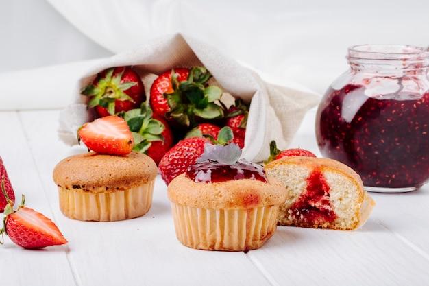 Cupcakes der seitenansicht mit erdbeermarmeladenbasilikum und frischer erdbeere auf weißem hintergrund