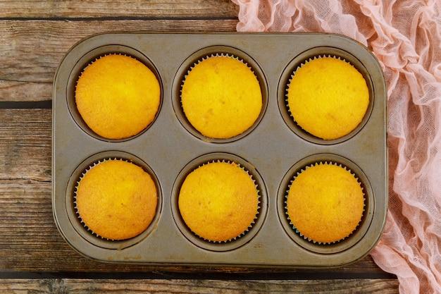 Cupcakes in der backform auf hölzernem hintergrund. draufsicht.