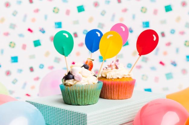 Cupcakes mit ballonspitzen auf blauem kasten