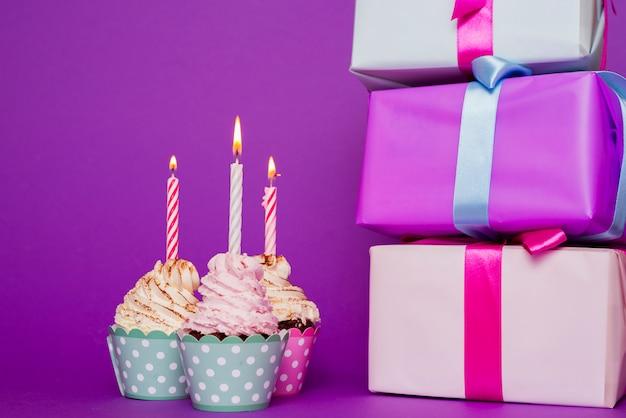 Cupcakes mit brennender kerze neben geschenken