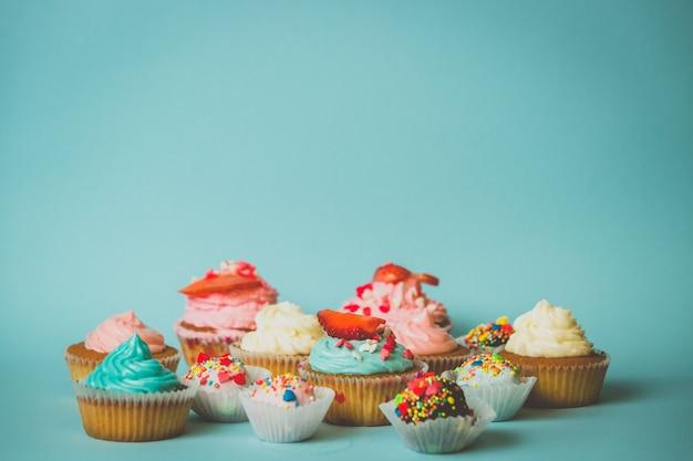 Cupcakes mit erdbeeren und bonbons mit streuseln auf blauem hintergrund