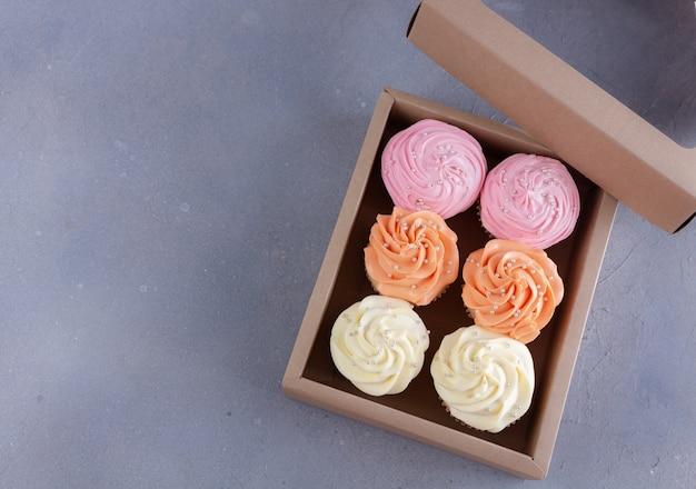Cupcakes mit farbcreme in geschenkbox mit kopierraum.