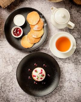 Cupcakes mit geschlagener weißer vanillecreme mit pfannkuchen und beerenmarmelade, eine tasse black coffee americano zum frühstück