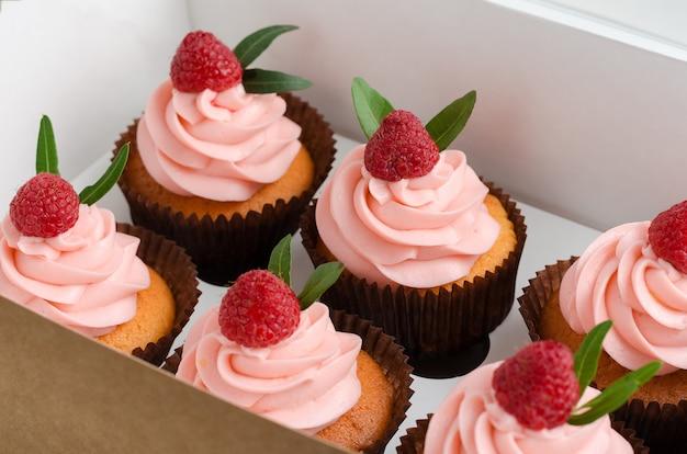 Cupcakes mit himbeercreme, verziert mit himbeeren oben auf geschenkpapier.
