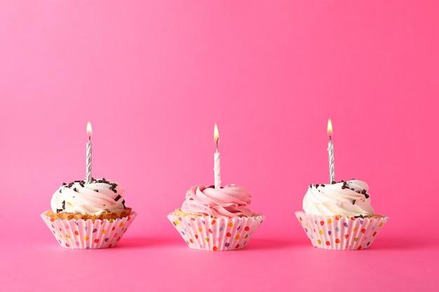 Cupcakes mit kerze auf rosa hintergrund, platz für text