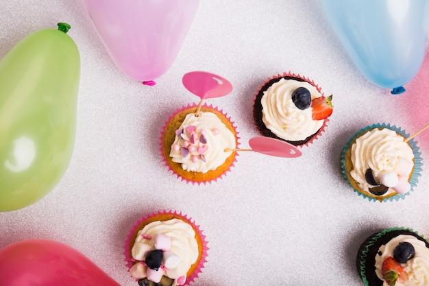 Cupcakes mit luftballons auf leuchttisch