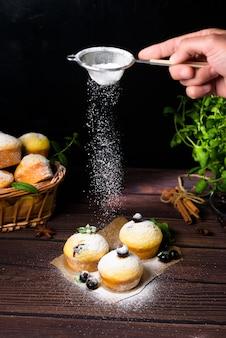 Cupcakes mit minze und schwarzen johannisbeerblättern in puderzucker auf schwarzem hintergrund, ein holzkorb mit cupcakes und schwarzen johannisbeeren. schweben von puderzucker auf muffins