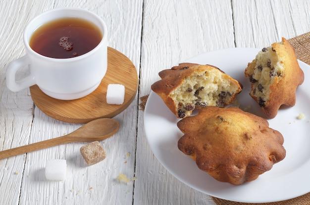 Cupcakes mit rosinen und tasse tee auf weißem holztisch