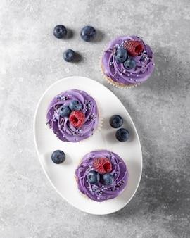 Cupcakes mit sahne auf einem weißen teller