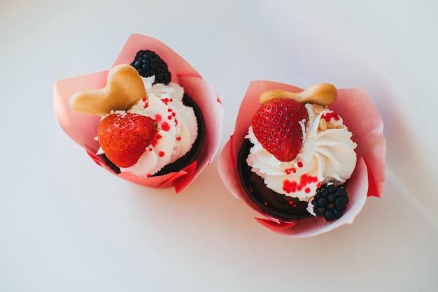 Cupcakes mit sahne und frischen erdbeeren und blackberry