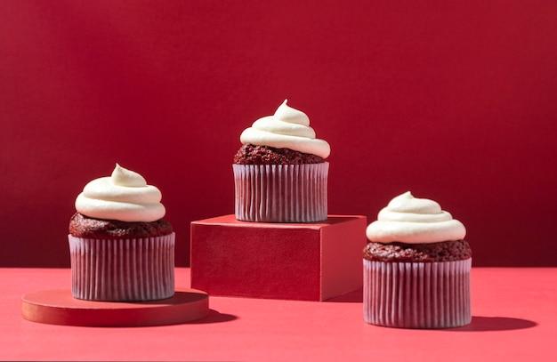 Cupcakes mit sahne und rotem hintergrund