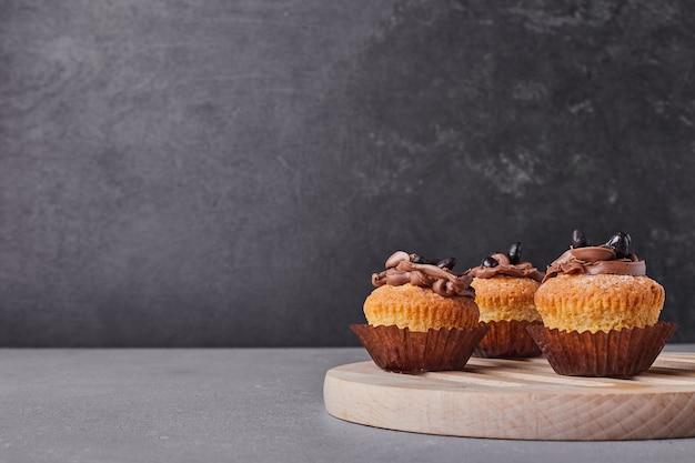 Cupcakes mit schokoladencreme auf holzplatte.