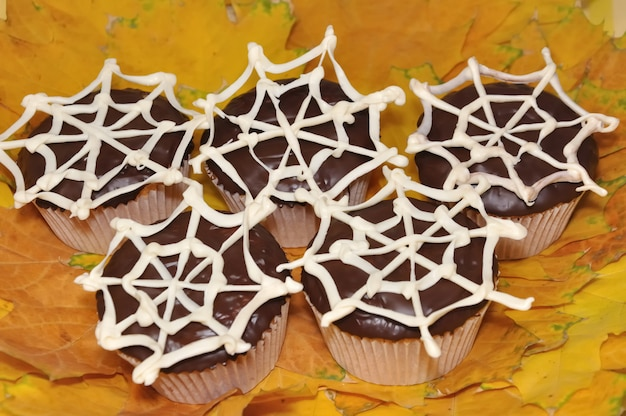 Cupcakes mit schokoladenglasur mit einem netzwerk aus weißer schokolade auf einem hintergrund von herbstblättern