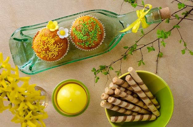 Cupcakes mit streuseln und blüten von mastix auf einem teller aus flasche auf einem tisch kithchen verziert
