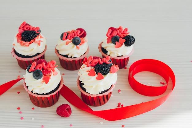 Cupcakes mit weißer sahne, frischen beeren und dekoration