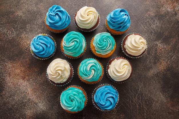 Cupcakes mit zuckerguss aus türkis und weißer buttercreme