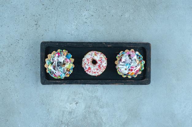 Cupcakes und donuts mit süßigkeiten auf einem schwarzen tablett auf marmoroberfläche