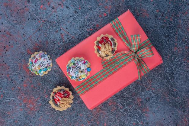Cupcakes und ein geschenkpaket auf abstraktem tisch.