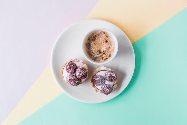 Cupcakes und kaffee auf tri farbigem hintergrund