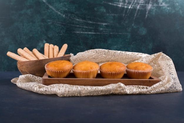 Cupcakes und waffelstangen auf einer holzplatte, winkelansicht