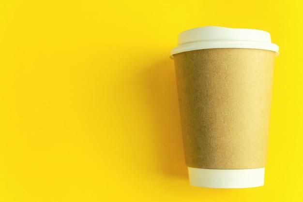Cupkaffee auf gelbem papierhintergrund
