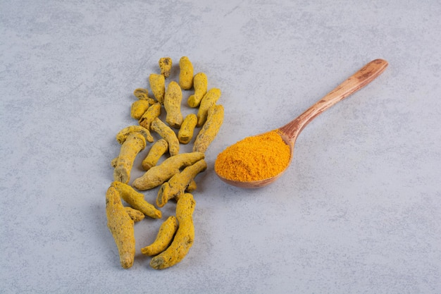 Curcuminpulver in einem holzlöffel gemischt.