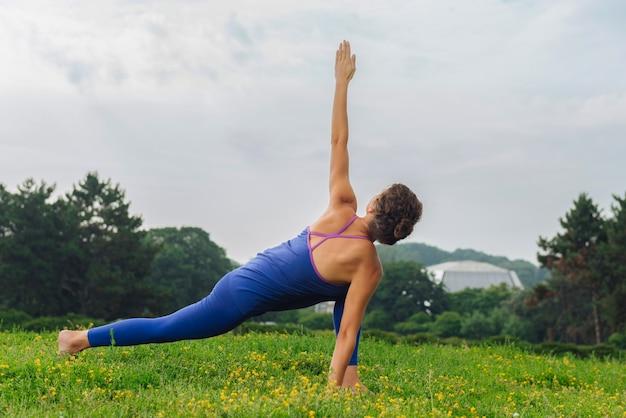 Curly athletische frau, die yoga liebt, das sonnengruß auf natur an ihrem wochenendmorgen tut